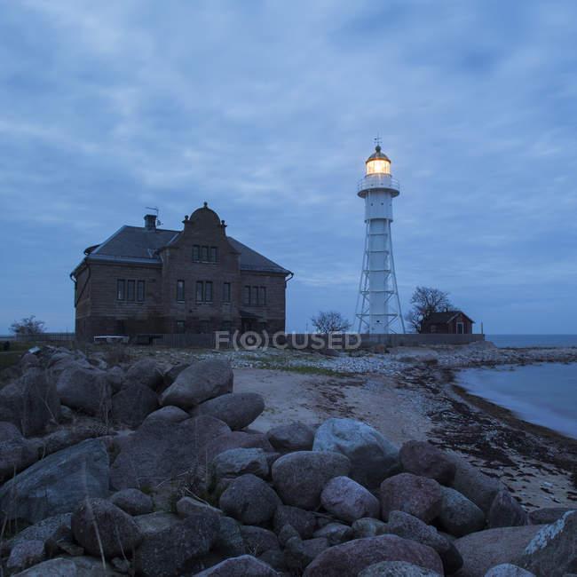Illuminated Lighthouse and buildings on beach at dusk — Stock Photo