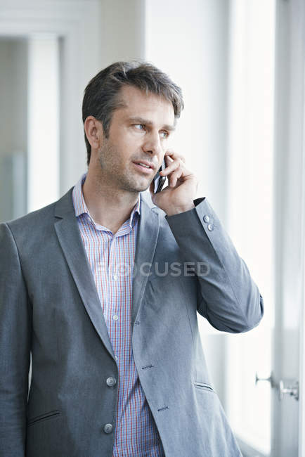 Mature businessman in formal wear talking on mobile phone — Stock Photo