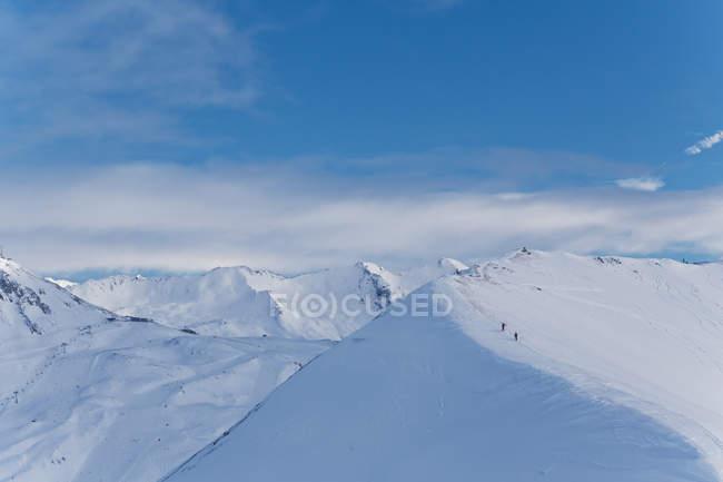 Vista panorámica de montañas nevadas con excursionistas distantes - foto de stock