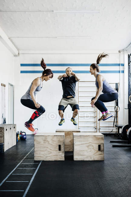 Young women and man jumping in gym — Stock Photo