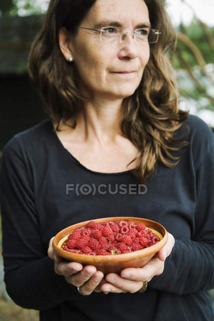 Mujer madura sosteniendo tazón de frambuesas - foto de stock
