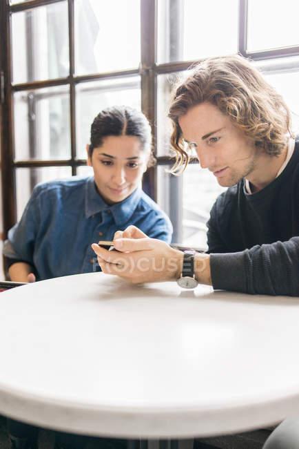 Молодые люди, глядя на мобильный телефон в кафе — стоковое фото