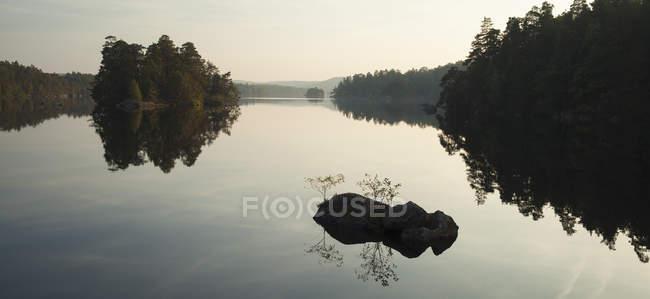Árvores silhuetas e rochas reflexos na água do lago — Fotografia de Stock