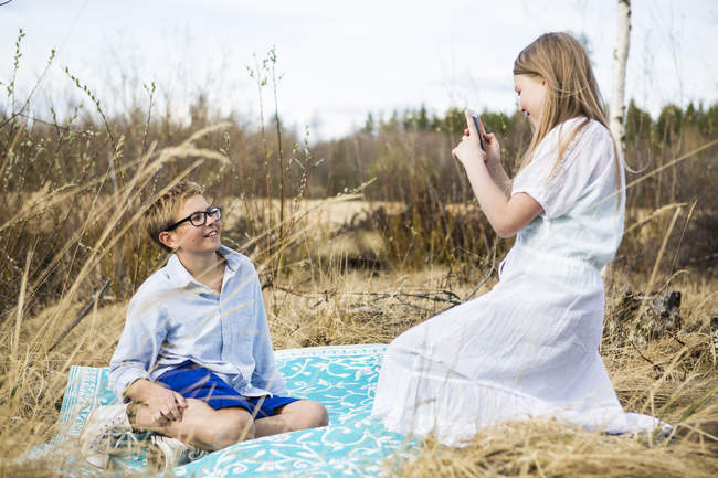 Girl photographing boy on smartphone at countryside — Stock Photo