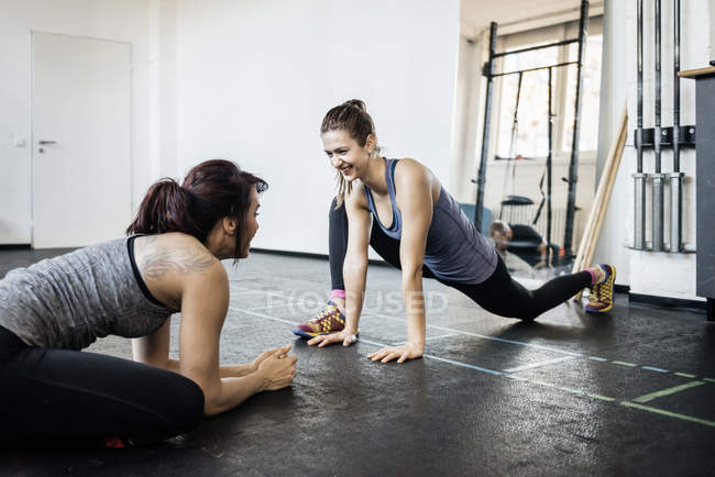 Two young women stretching in gym — Stock Photo