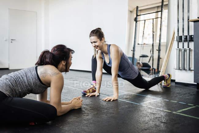 Dos mujeres jóvenes que se extiende en gimnasio - foto de stock