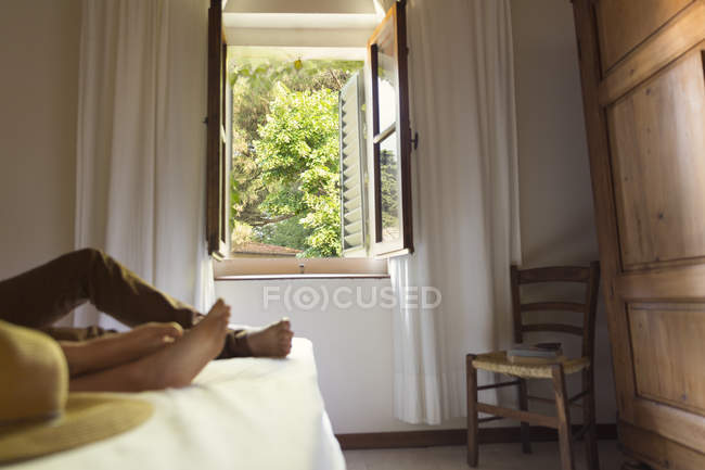 Couple lying on bed in farmhouse — Stock Photo
