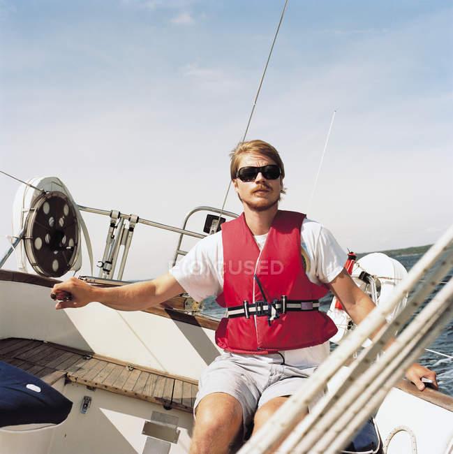 Homem adulto médio na popa do veleiro, foco diferencial — Fotografia de Stock