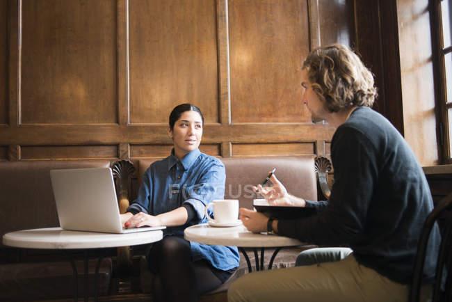 Двое молодых людей, работающих в кафе — стоковое фото