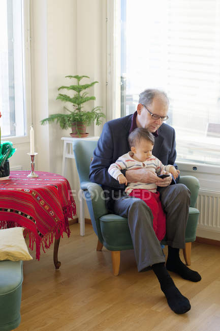 Senior man sitting in armchair and holding grandson on laps — Stock Photo