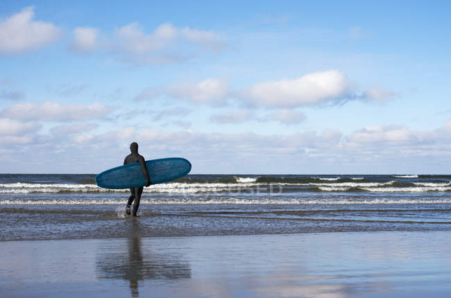 Rear view of surfer in wetsuit on beach — Stock Photo
