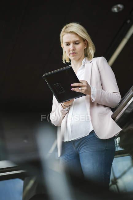 Jovem empresária usando tablet digital, foco diferencial — Fotografia de Stock