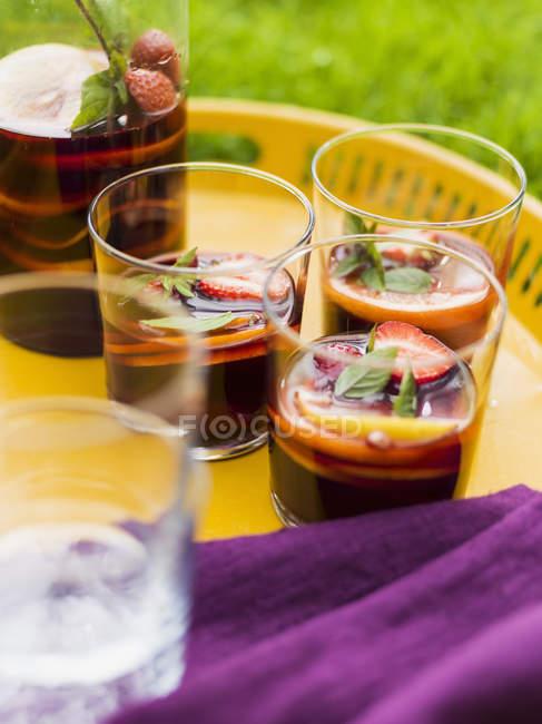 Vasos con bebidas sangría en bandeja - foto de stock