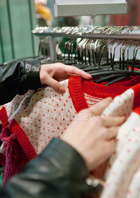 Жінка тримає вибір одягу в магазині — стокове фото
