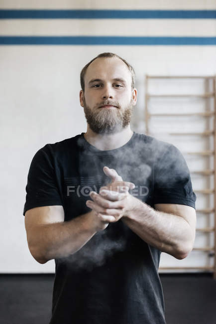 Bearded man chalking hands in gym — Stock Photo