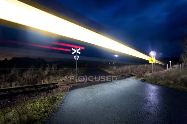 Light trails of passing train and warning signs at night — Stock Photo