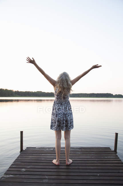 Rear view of woman raising arms on jetty — Stock Photo