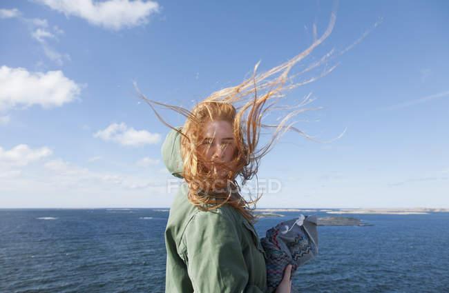 Junge glückliche Frau steht am Meer — Stockfoto