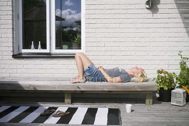 Seitenansicht der reifen Frau auf Bank liegend — Stockfoto
