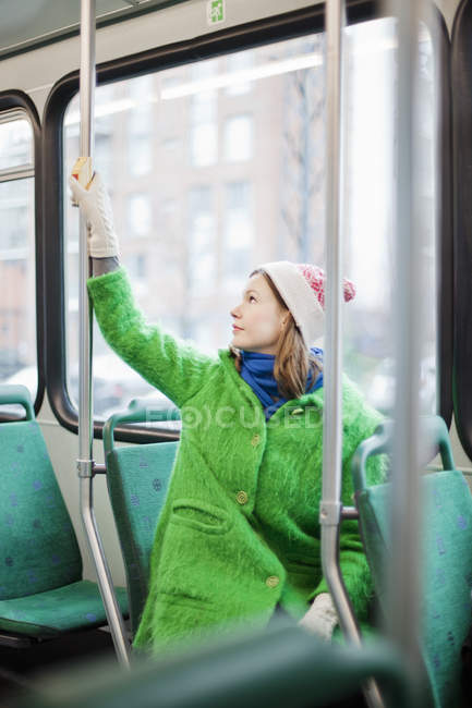 Young woman pressing request stop button in tram — Stock Photo