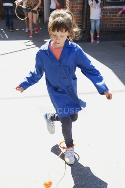Vue de face de jeune fille sautant dans Cour d'école — Photo de stock