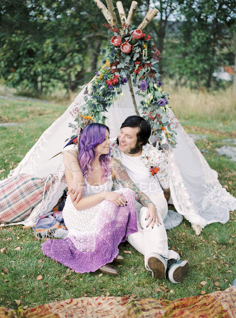 Bride and groom sitting on grass in front of white tent at hippie wedding — Stock Photo