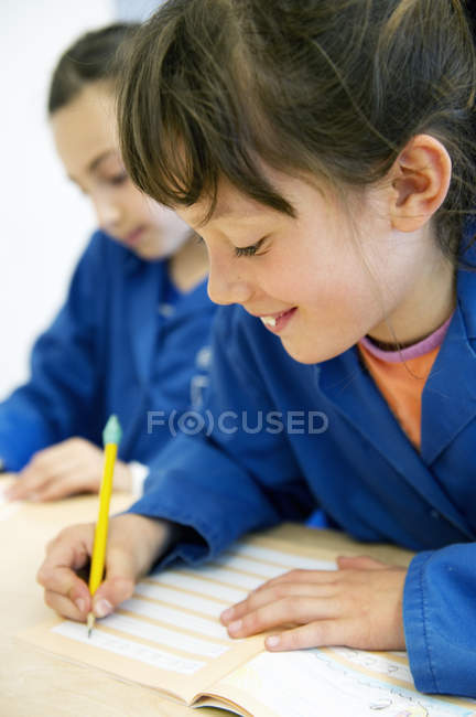 Two girls writing in classroom, focus on foreground — Stock Photo