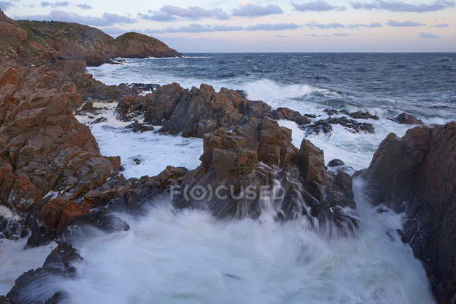 Surf wave breaking against coastline rocks — Stock Photo