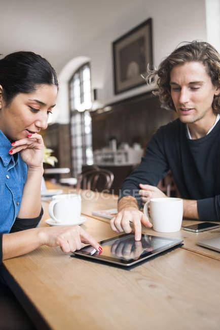 Молодых людей, используя цифровые планшетные в кафе — стоковое фото