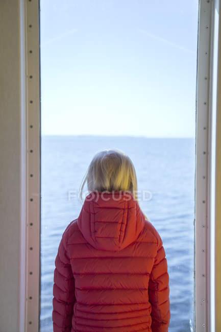 Fille regardant par la fenêtre, vue arrière — Photo de stock