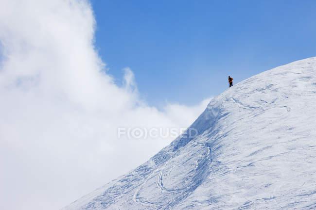 Sommet de montagne enneigé avec randonneur lointain — Photo de stock