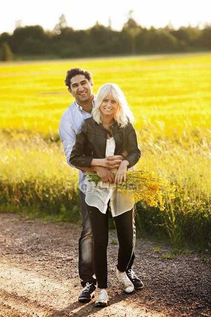 Jeune couple souriant embrassant par champ, se concentrer sur le premier plan — Photo de stock