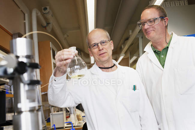 Scientists with laboratory flask, differential focus — Stock Photo