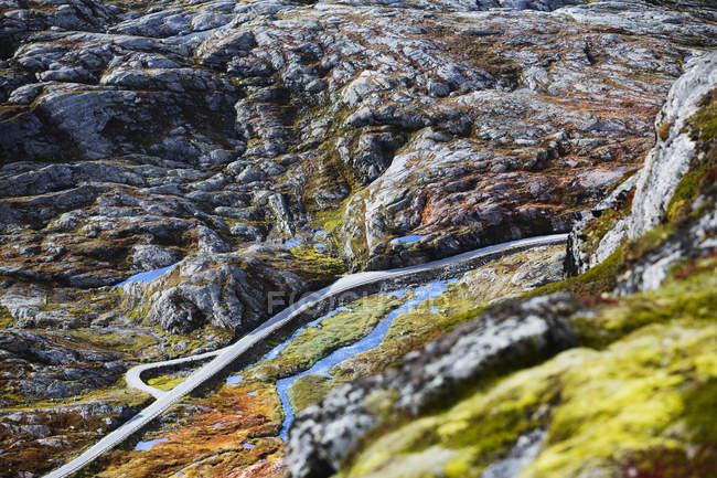 Дорога тянется через освещенную солнцем горную долину — стоковое фото