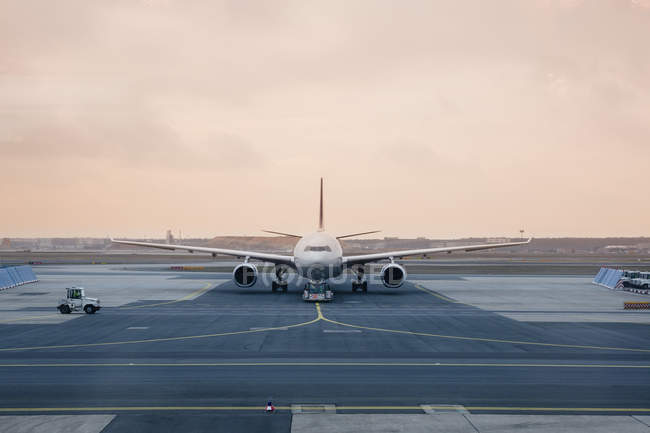 Front view of airplane on runway at dusk — Stock Photo