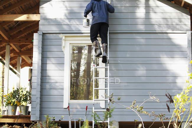 Visão traseira do homem em botas de borracha na escada — Fotografia de Stock