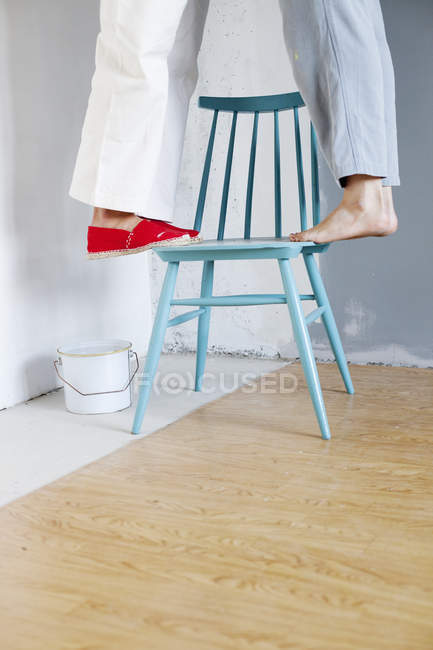 Women standing on one chair by paint can — стокове фото