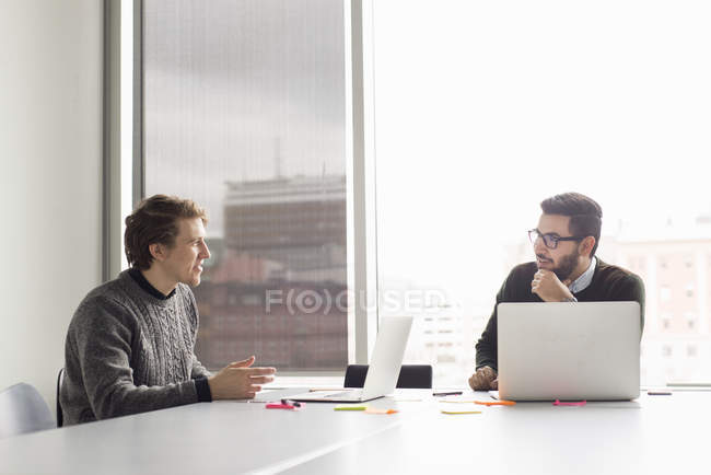 Two men talking while sitting in office with laptops — Stock Photo