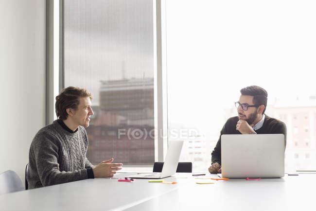 Двое мужчин говорить сидя в офисе с ноутбуками — стоковое фото