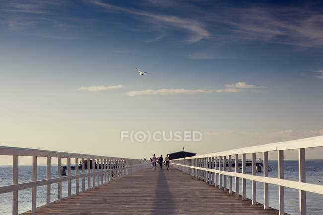 Women walking on pier, diminishing perspective — Stock Photo