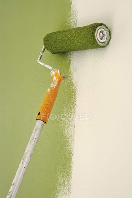 Крупним планом малярні валики на частково пофарбовані стіни — стокове фото