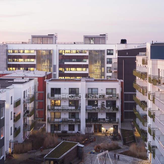 Wohnviertel mit beleuchteten Fenstern bei Sonnenuntergang — Stockfoto