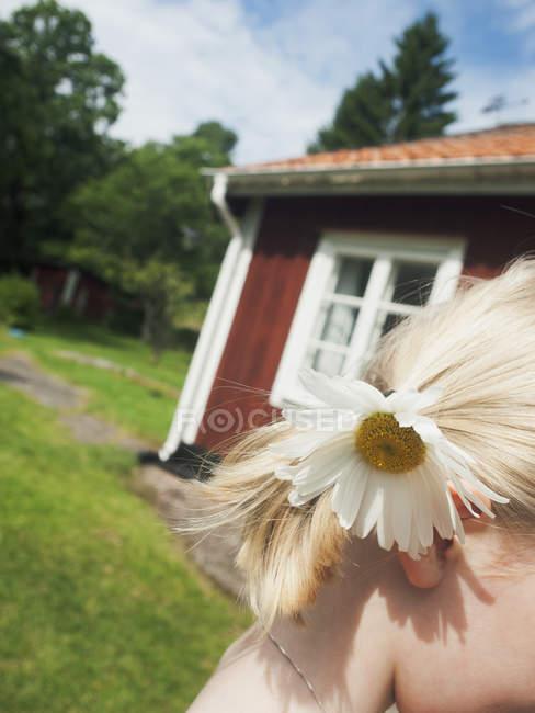 Niña con flor en el pelo rubio, enfoque selectivo - foto de stock