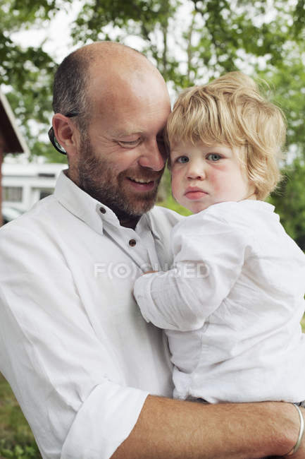 Man carrying grandson, focus on foreground — Stock Photo