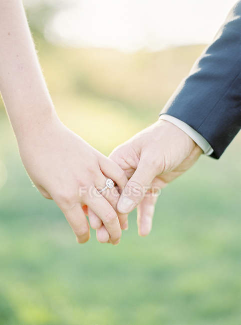 Cropped view of holding hands of newlyweds, selective focus — Stock Photo