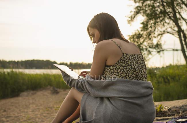 Giovane donna che si siede sul lungolago e utilizza la compressa di digital — Foto stock