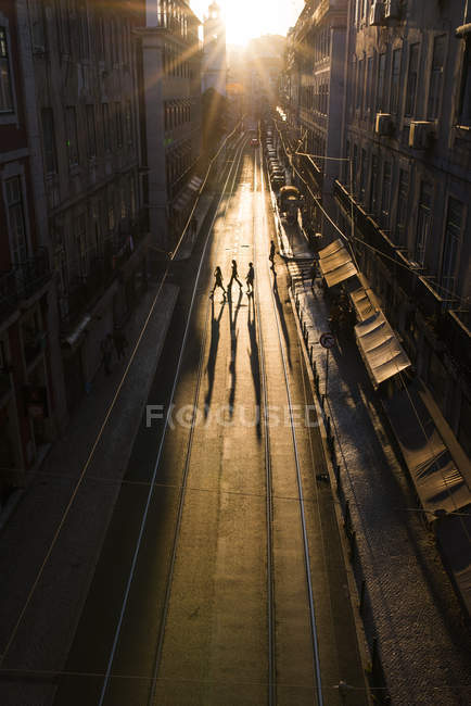 Silhouettes of four pedestrians crossing empty street in Portugal — Stock Photo