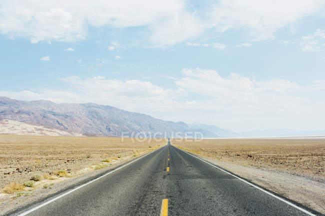 Порожній дороги і гори при яскравому сонячному світлі — стокове фото