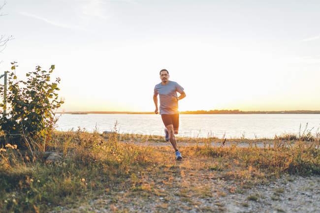 Середині дорослої людини біг на березі моря — стокове фото