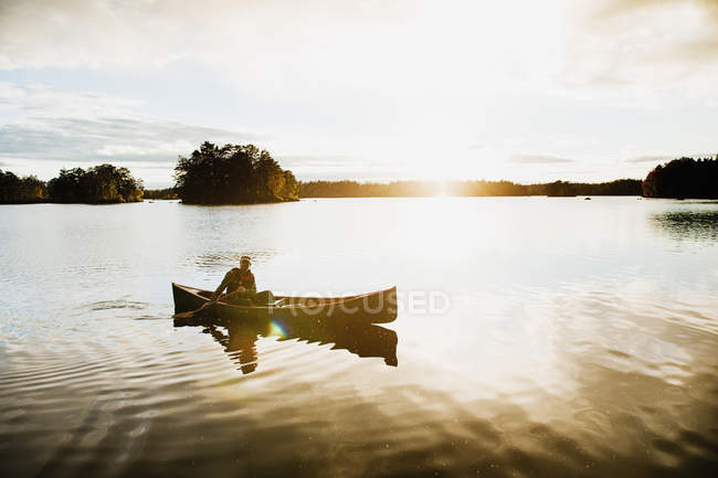 Man paddling canoe on lake, kingdom of sweden — Foto stock